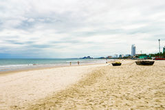 Palm boats and tourists at the China Beach in Danang. In Vietnam. It is also called Non Nuoc Beach. South China Sea and Marble Mountains on the background Royalty Free Stock Photo