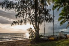 Palm Cove Beach at Sunrise with Palm Trees and Sailboats Royalty Free Stock Photos
