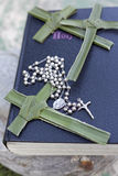 Palm cross, rosary beads sitting on a Bible. A closed bible with rosary beads and palm crosses on it Stock Photos