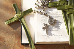 Palm cross, rosary beads sitting on an open Bible. An open bible with palm crosses and set of rosary beads on it Stock Image