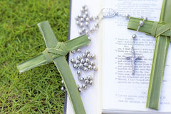 Palm cross, rosary beads sitting on an open Bible. A bible sitting on grass with palm crosses and a set of rosary beads Stock Image