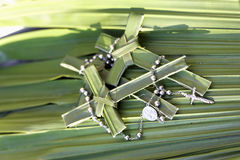 Palm crosses and rosary beads on palm leaves. 3 palm crosses with rosary beads on a bad of palm leaves stock images