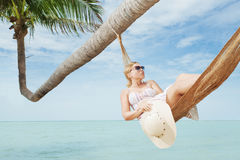 Palm delight. View of nice young lady swinging  in hummock on tropical beach Stock Photos