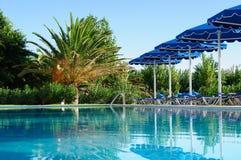 Palm en zonparaplu's door de pool, Griekenland stock foto's
