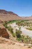 Palm fodrade torr flodsäng med röda orange berg nära Tiznit i Marocko, Nordafrika arkivbild