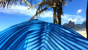 Palm Frond Shadows Rio de Janeiro Brazil. Palm frond shadows fluttering on blue umbrella in front of a bright scenic view of Ipanema Beach in Rio de Janeiro stock video footage