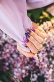 Girl`s palms in delicate color with a bouquet of flowers stock images
