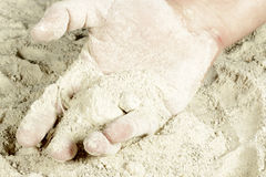 The palm of a hand covered with sand Stock Photo