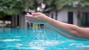 In the palm of the hand men recruited water and poured into the hotel pool. Blue water stock video