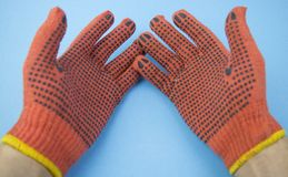 Palm of hands in working gloves on blue background stock image