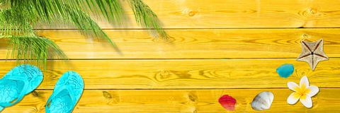 Palm leaf, flip flops and seashells on yellow wooden planks, panoramic beach and summer background royalty free stock photo