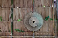 Palm leaf hat hanging on the thatch wall, the weave hat for Thai royalty free stock photos