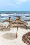 Palm leaf parasols on sea shore Royalty Free Stock Photo