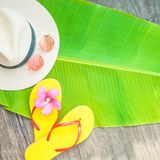 Palm leaf Straw hat Pink sunglasses Beach flip-flops Summer background. Copy space Top view stock images