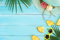 Palm leaves, straw hat, pineapple slices and sunglasses on wood plank blue color. Royalty Free Stock Photo