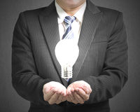Palm opening business man with lighting bulb. Palm opening business man with lighting blub in gray concrete background Royalty Free Stock Images