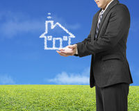 Palm opening businessman with cloud shape house in green meadow. And blue sky background Royalty Free Stock Image