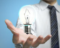 Palm opening Businessman with lighting lamp. In blue background Royalty Free Stock Image