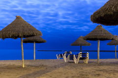 Palm parasols and beach loungers on moonlight beach. Palm parasols against cloudy night sky on moonlight beach Royalty Free Stock Image