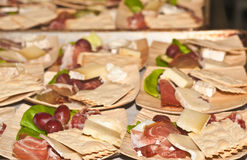 Palm plates with organic food for a tasting. Wine tasting food pairings on palm tree plates of sliced salami, italian ham, prosciutta, red grapes slices of Royalty Free Stock Image