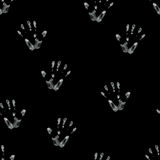 Palm print drawn in chalk. Seamless hand drawn pattern of palm imprints drawn in white chalk isolated on black background Royalty Free Stock Images