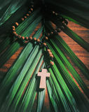 Palm Sunday - Retro. Palm Sunday still life - A beaded olive wood cross or rosary rests upon a palm branch on top of a rustic table.  Processed for an aged