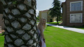 Palm tree and blond lady flirting. Lady is sending kisses, smiling and flirting. There is huge palm tree trunk, grass, blue summer sky and houses in the stock video