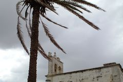palm tree and church with bad weather in the historic center of Otranto - Italy Royalty Free Stock Photos