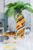 Palm tree exotic fruits. Palm tree decorated with exotic fruits on sticks stands on the wedding stock photos