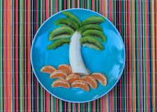 Palm tree from fruits. Palm tree from kiwis, banana, and tangerines on a blue plate Royalty Free Stock Photography