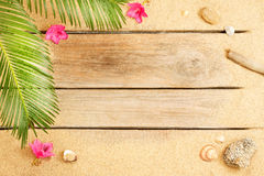 Palm tree leaves and sand on wood background - beach Royalty Free Stock Photography