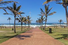 Palm Tree Lined Walkway Heading Toward  Blue Coastal Skyline. Concrete palm tree lined walkway heading toward beach sea and blue coastal skyline in Durban, South Royalty Free Stock Images