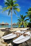 Tahitian boat on Bora Bora. Palm tree with overwater bungalows in background and authentic style canoe on Bora Bora royalty free stock photos