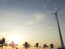 Palm tree silhouette with wind turbine. Sunset time Royalty Free Stock Image
