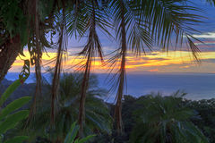 Palm Tree Sunset HDR. Empty chairs under a plam tree on a poolside 'beach' overlooking the Pacific Ocean and Nicoya Peninsula at sunset near Tarcoles, Costa Rica Stock Photos