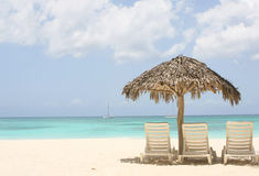Palm tree and two chairs on sand. Beach with palm tree and two chairs on sand stock image