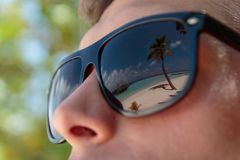 Palm tree, white beach and crystal clear blue water reflected in the sunglasses of a man. Maldives royalty free stock photo