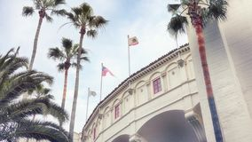 Palm trees, building, California & American Flag royalty free stock image