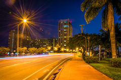 Palm trees and buildings along Dade Boulevard at night, in Miami. Beach, Florida Royalty Free Stock Photo