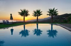 Palm Trees and Pool in an Aegean sunrise Stock Photo