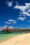 Palm trees and small houses on water.Polynesia Stock Photography