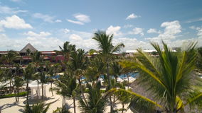 Palm trees, sun chairs, white sand, swimming pools on Punta Cana beach. Luxury resort.