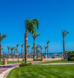View of the hotel's recreation area on the beach and the sea shore, palm trees under the blue sky of a sunny day stock photos