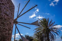 Palm trees and windmills on a blue sky background. Sunny summer day, view of very old windmills, beautiful blue sky with some white clouds; palm trees and Royalty Free Stock Photos