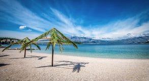 Palm umbrellas on beach in Croatia Stock Photos