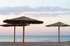 Palm umbrellas on the beach Royalty Free Stock Photos