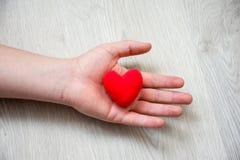In palm van hand die op houten vloer liggen, is anatomisch model van hart Conceptenfoto die zulk een hart of cardivascular ziekte royalty-vrije stock foto's