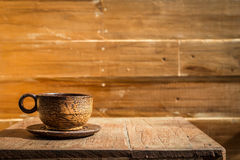 Palm wood coffee cup on wooden table and wooden wall Royalty Free Stock Images