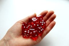 On the palm of your hand there are red bones playing. Background, dice, game, red, isolated, white, games, cube, bones, play, number, luck, gambling, six royalty free stock photo