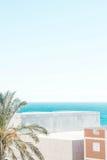 Palma, costruzioni e mare Immagini Stock